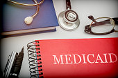 Titled red book medicaid along with medical equipment, conceptual image