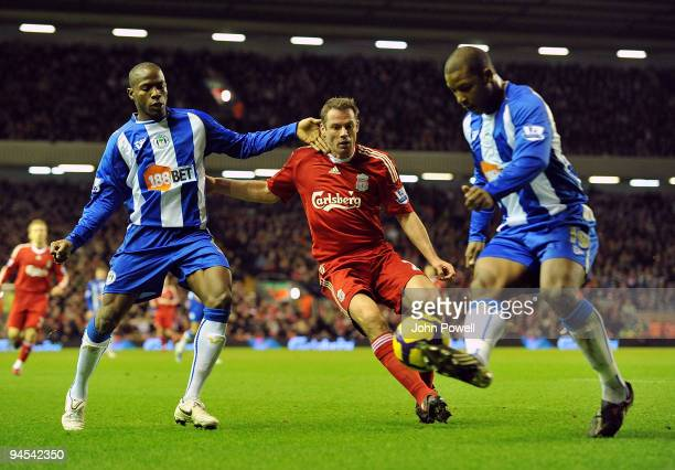 Titus Bramble of Wigan kicks the ball away from Jamie Carragher of Liverpool during the Barclays Premier League match between Liverpool and Wigan...