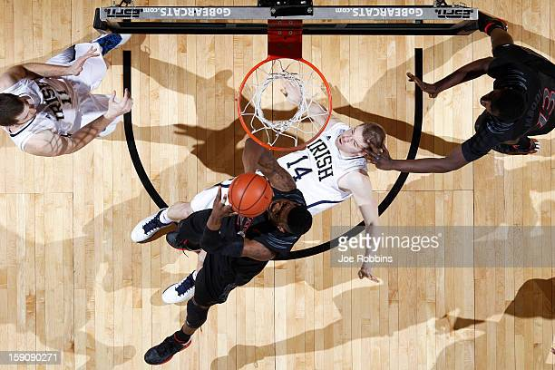 Titus Rubles of the Cincinnati Bearcats goes up for a shot against Scott Martin of the Notre Dame Fighting Irish during the game at Fifth Third Arena...