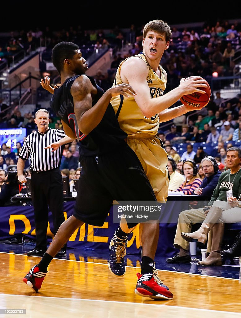 Titus Rubles #2 of the Cincinnati Bearcats guards as Jack Cooley #45 of the Notre Dame Fighting Irish tries to pass off the ball at Purcel Pavilion on February 24, 2013 in South Bend, Indiana. Notre Dame defeated Cincinnati 62-41.