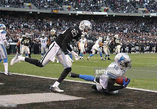 Titus Young of the Detroit Lions catches a touchdown in front of DeMarcus Van Dyke of the Oakland Raiders at Oco Coliseum on December 18 2011 in...