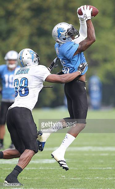Titus Young of the Detroit Lions makes the catch over Ross Weaver during the morning practice sessions on August 14 2012 in Allen Park Michigan