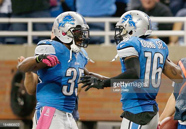Titus Young scores on a one yard touchdown pass from Matthew Stafford and is congratulated by teammates Joique Bell during the game against the...