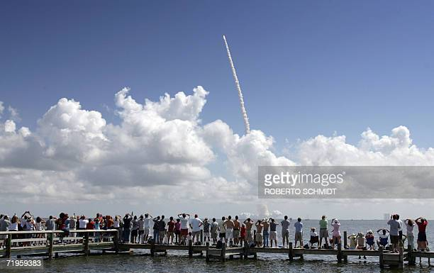 Spectators at the Indian River Estuary in Titusville Florida watch 09 September 2006 the Space Shuttle Atlantis lift off from launch pad 39B at the...