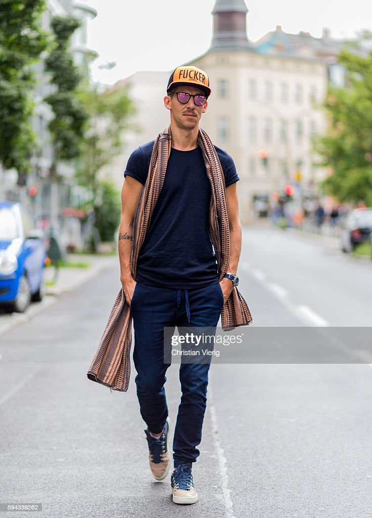 Tjalle Story wearing a yellow trucker cap navy tshirt scarf blue pants sunglasses and court sneakers on August 22 2016 in Berlin Germany