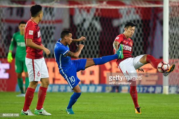 Tjaronn Chery of Guizhou Zhicheng competes for the ball with Xu Xin of Guangzhou Evergrande during their Chinese Super League football match in...