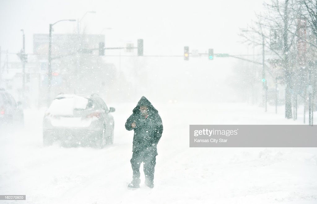 Tjuan Goodwin of Kansas City, Missouri walks in the street of Broadway Boulevard at 39th Street in near whiteout conditions during heavy snowfall that blanketed the metro area, Thursday, February 21, 2013.