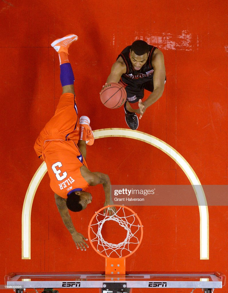 Warren #24 of the North Carolina State Wolfpack scores against Adonis Flyer #3 of the Clemson Tigers during play at PNC Arena on January 20, 2013 in Raleigh, North Carolina. North Carolina State won 66-62.