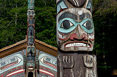 Tlingit totem pole with clan house in the background at the Totem Bight State Historical Park in Ketchikan Southeast Alaska USA