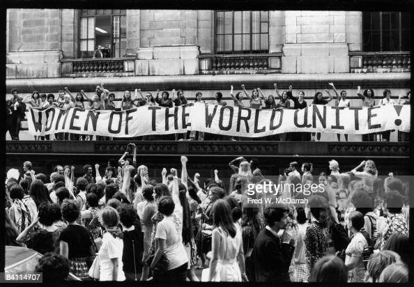 To commemorate the 50th anniversary of Women's Suffrage in the United States record numbers of women march along 5th Avenue past a banner that reads...