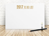 2017 To do list year text on white paper poster with black pencil and lightbulb on wood plank floor and white brick wall,Business presentation mock up for adding your list.