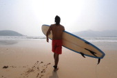 LIFESTYLECHINALEISURESURFING A surfer carries his board toward the waters of the South China Sea at Houhai Beach outside of Sanya on October 24 in...