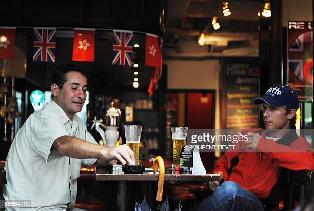 FINANCEECONOMYHEALTHSMOKING Men smoke cigarettes in a bar in in Hong Kong on June 27 2009 Hong Kong�s government is set to enforce a blanket smoking...