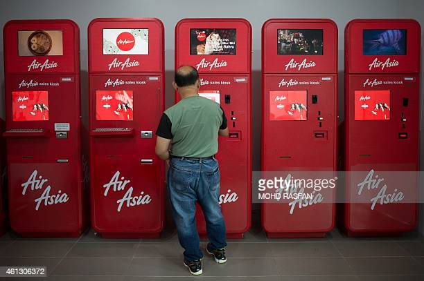 To go with AFP story IndonesiaMalaysiaSingaporeaviationAirAsiacompanyFOCUS by Satish Cheney This photo taken on January 10 2015 shows a man using an...