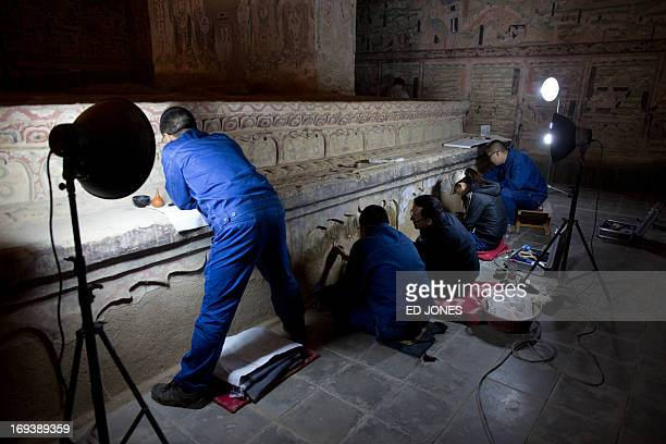 To go with AFP story ChinaheritagetechnologyartFEATURE by Sebastien Blanc In a photo taken on May 13 2013 technicians restore one of the Mogao caves...