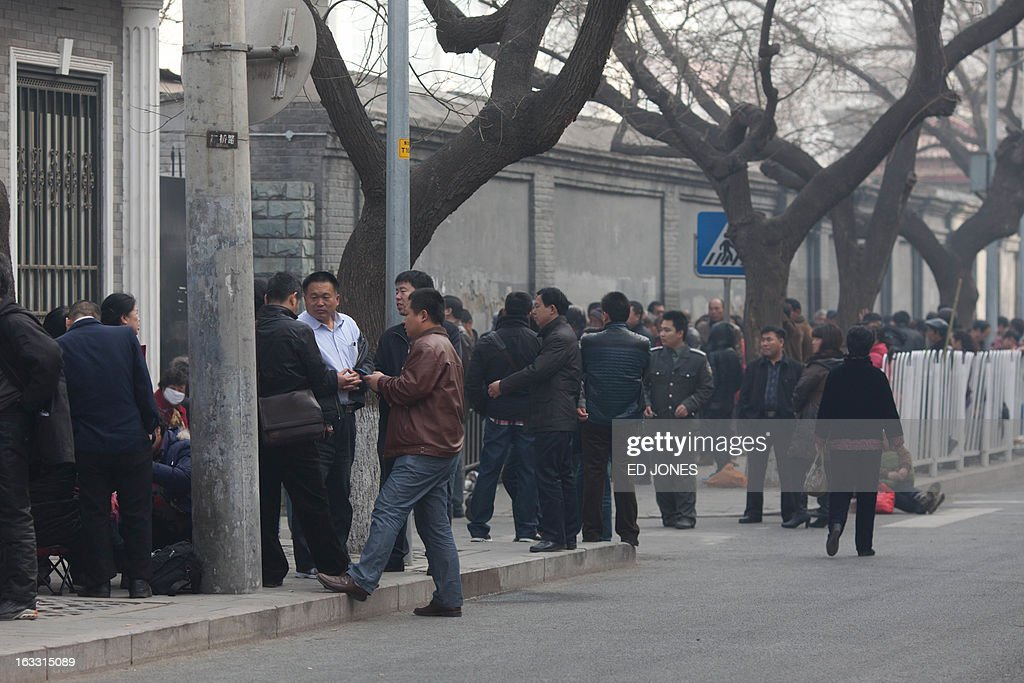 To go with AFP story 'ChinapoliticsCongressrightsFOCUS' by Carol Huang People stand on a street as they queue outside the petitions office in Beijing...