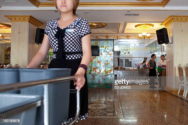 To go with AFP story ChinapoliticsFOCUS by Tom Hancock This photo taken on August 6 2012 shows waitress pushes a cart at a restaurant in the...