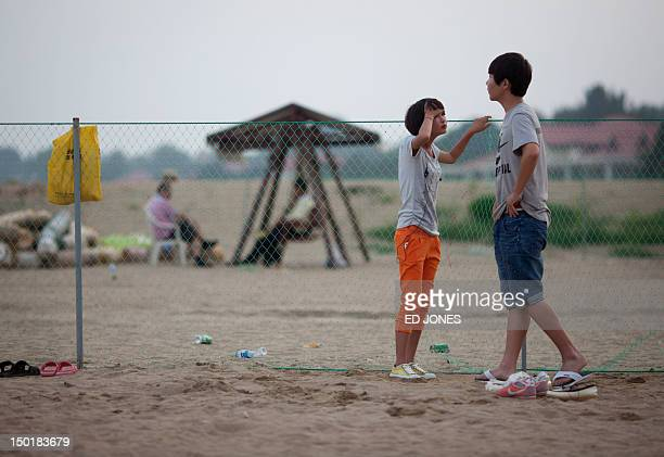 To go with AFP story ChinapoliticsFOCUS by Tom Hancock This photo taken on August 6 2012 shows a couple standing at a fence separating a public beach...