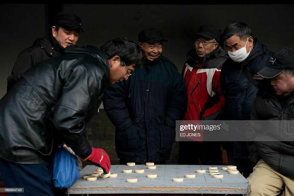 To go with AFP story 'China-population-labour-economy-social,FOCUS' by Fran wang Elderly men play a board game in a park in Beijing on January 30, 2012. China's demographic timebomb is ticking significantly louder with the first fall in its labour pool for decades, analysts say, highlighting the risk that the country grows old before it grows rich. AFP PHOTO / Ed Jones