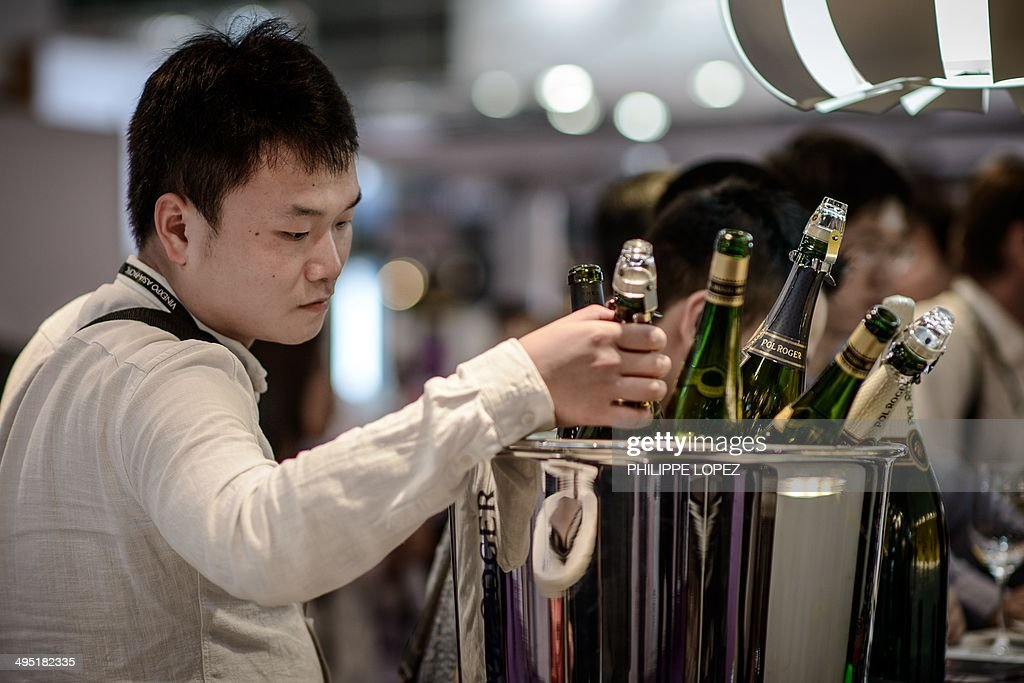 To go with AFP Story France-Asia-wine-lifestyle-Economy,FOCUS by Gael Branchereau This picture taken on May 27, 2014 shows a visitor checking bottles of Champagne at Vinexpo Asia Pacific in Hong Kong. 'It's only champagne if it's from Champagne' may be a motto that is gradually being adopted in China, but much remains to be done to protect the most copied wines and grand crus. AFP PHOTO / Philippe Lopez