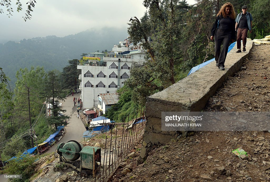 To go with AFP story 'India-Tibet-travel-tourism-religion,FEATURE' by Ben Sheppard This picture taken on September 28, 2012 shows a foreign tourists walking at a hillside construction site in McLeod Ganj, Dharamshala. Once the refuge of pious Tibetan monks and a few hippie travellers, Dharamshala in the Himalayan foothills is today a crowded and chaotic town where long-term residents fear for its future. AFP PHOTO / Manjunath KIRAN