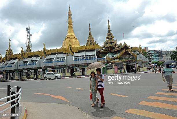 To go with AFP story MyanmarreligionmarriageFOCUS by Nan Tin Htwe In this photo taken on June 17 a couple cross a road before Sule pagoda in Yangon...