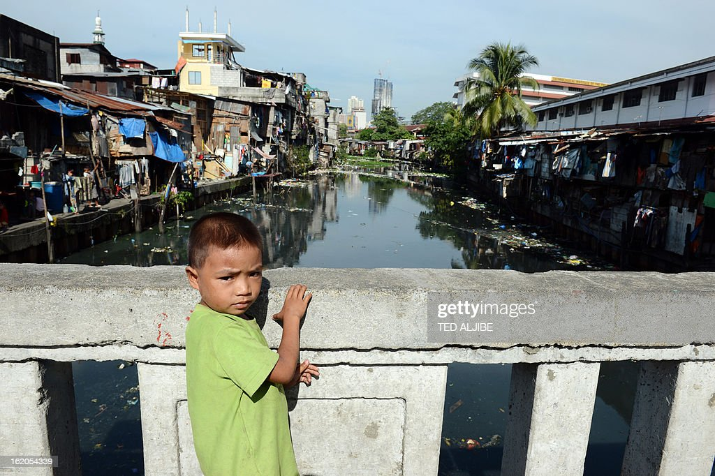 To Go With AFP story 'Philippines-Environment-Pollution-Water-Poverty' by Karl Malakunas In this picture taken on February 18, 2013, a boy stands along a bridge next to stilt houses, one of the many areas along waterways in Manila. At Estero de Paco, a 2.9-kilometre (1.8-mile) tributary that a few years ago was one of the most polluted in the city, shanty homes have been replaced with tree-lined boardwalks while water-treatment machines now nestle amid plants.