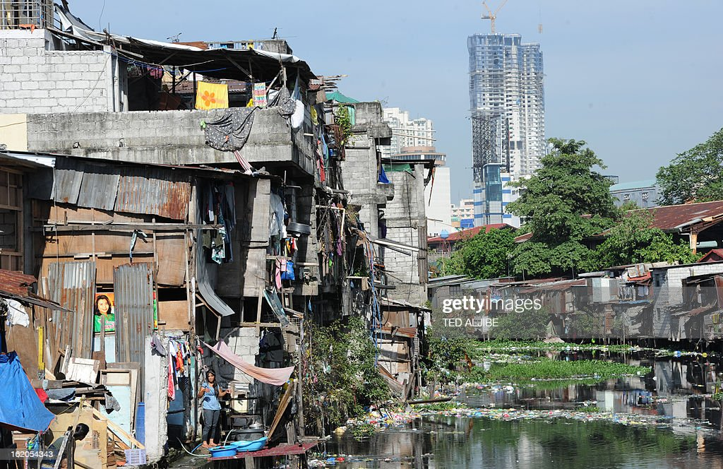 To Go With AFP story 'Philippines-Environment-Pollution-Water-Poverty' by Karl Malakunas In this picture taken on February 18, 2013, a general view of informal settlers' homes along a waterway in Manila. At Estero de Paco, a 2.9-kilometre (1.8-mile) tributary that a few years ago was one of the most polluted in the city, shanty homes have been replaced with tree-lined boardwalks while water-treatment machines now nestle amid plants. AFP PHOTO/TED ALJIBE