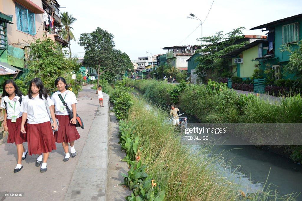 To Go With AFP story 'Philippines-Environment-Pollution-Water-Poverty' by Karl Malakunas In this picture taken on February 18, 2013, students walk to school along Estero de Paco tributary in Manila. At Estero de Paco, a 2.9-kilometre (1.8-mile) tributary that a few years ago was one of the most polluted in the city, shanty homes have been replaced with tree-lined boardwalks while water-treatment machines now nestle amid plants.