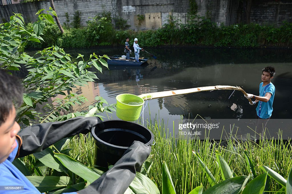 To Go With AFP story 'Philippines-Environment-Pollution-Water-Poverty' by Karl Malakunas In this picture taken on February 18, 2013, students from a nearby university collect water samples along Estero de Paco tributary in Manila. At Estero de Paco, a 2.9-kilometre (1.8-mile) tributary that a few years ago was one of the most polluted in the city, shanty homes have been replaced with tree-lined boardwalks while water-treatment machines now nestle amid plants. AFP PHOTO/TED ALJIBE