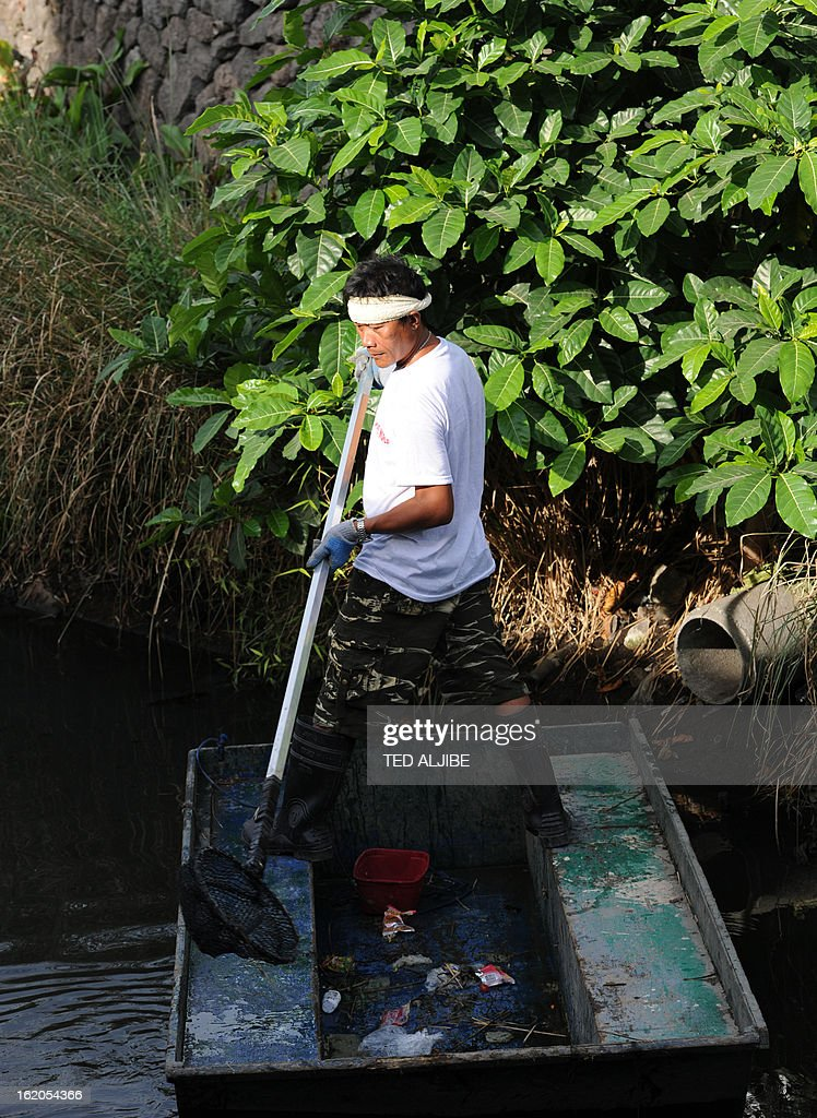 To Go With AFP story 'Philippines-Environment-Pollution-Water-Poverty' by Karl Malakunas In this picture taken on February 18, 2013, a volunteer cleans along Estero de Paco tributary in Manila. At Estero de Paco, a 2.9-kilometre (1.8-mile) tributary that a few years ago was one of the most polluted in the city, shanty homes have been replaced with tree-lined boardwalks while water-treatment machines now nestle amid plants.