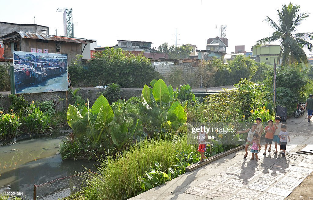 To Go With AFP story 'Philippines-Environment-Pollution-Water-Poverty' by Karl Malakunas In this picture taken on February 18, 2013, children walk along Estero de Paco tributary amid lush greenery in Manila. At Estero de Paco, a 2.9-kilometre (1.8-mile) tributary that a few years ago was one of the most polluted in the city, shanty homes have been replaced with tree-lined boardwalks while water-treatment machines now nestle amid plants.