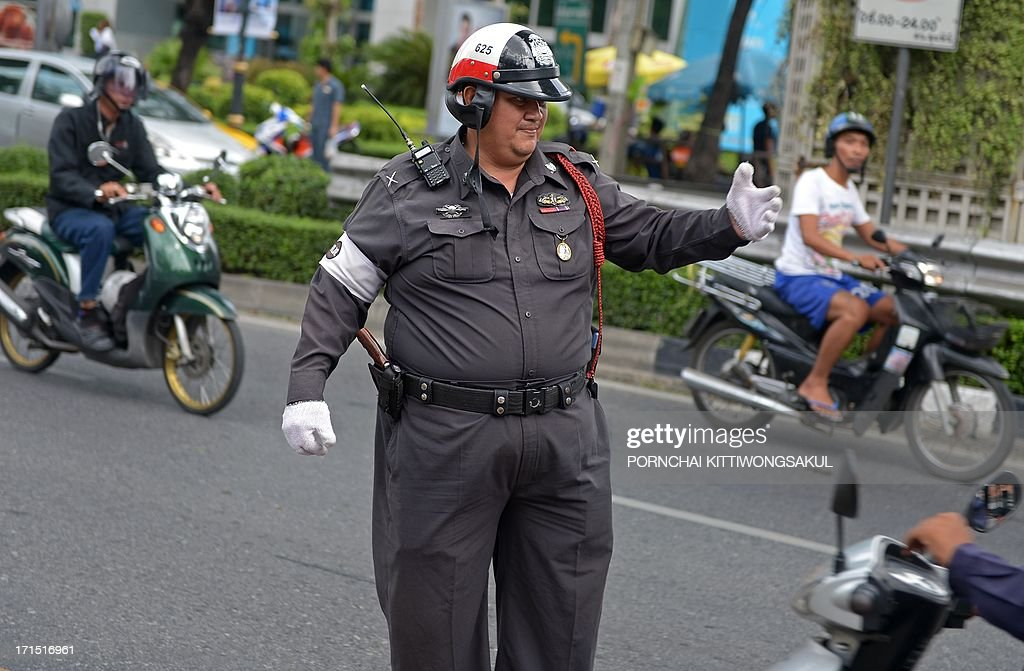 To go with AFP story Thailand-lifestyle-health-police by Apilaporn VECHAKIJ In a pictire taken on June 24, 2013, a Thai traffic policeman directs traffic on a street in Bangkok. Bellies wobbling and chubby limbs swinging, dozens of sweaty traffic cops exercise to the rhythm of Thai pop songs as part of a scheme to reduce the number of overweight police in Bangkok.