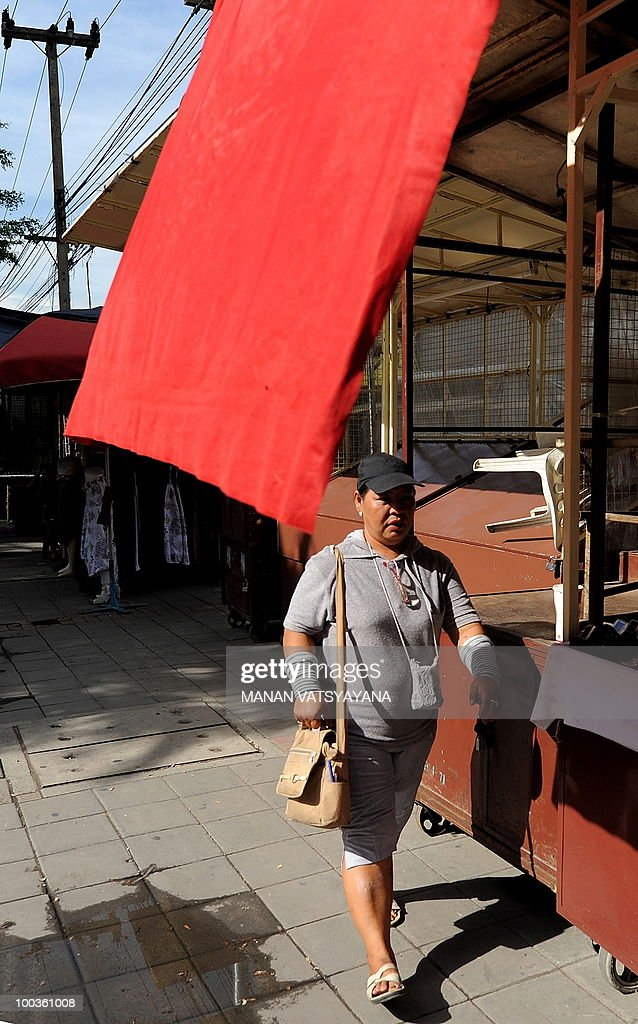 Thailand-politics-protest-north, FOCUS, by M. Jegathesan In this picture taken May 22, 2010, Thai woman Saisunee Assawasunthornkul walks past a red flag at a street market in Chiang Mai around 700kms from Bangkok.Frustrated, homeless and bitterly disappointed -- this is the reality for 'Red Shirt' Parichart Chanmanee as she returns to her northern hometown after two months of protesting in Bangkok. The single mother-of-two made the long journey back by bus on Thursday after a deadly military crackdown forced the anti-government movement's leaders to surrender, sparking looting and major arson attacks by hardcore protestors.