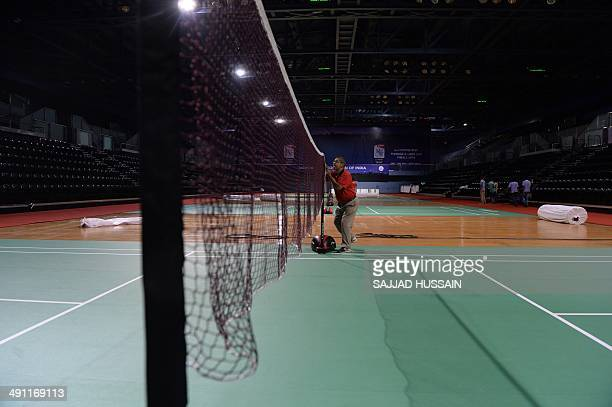 To go with 'BadmintonSuper Dan to light up China's record bid' PREVIEW by Kuldip Lal An Indian official adjusts a net on a badminton court at The...