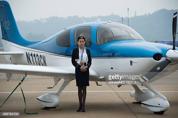 To go with Chinaeconomyaviation by Bill SAVADOVE A model poses in front of a Cirrus SR22 aircraft at the Airshow China 2014 in Zhuhai south China's...