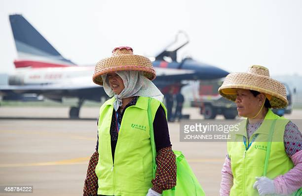 To go with Chinaeconomyaviation by Bill SAVADOVE Cleaning women pass a J10 fighter jet of the Bayi Aerobatic Team of the PLA's Air Force at the...