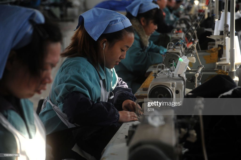To go with 'China-economy-growth,ANALYSIS' by Kelly Olsen This picture taken on January 10, 2013 shows laborers working in a clothing factory in Huaibei, central China's Anhui province. China's economy is poised finally to end a long downward trend in 2013, economists polled by AFP say, as the new communist leadership vows to retool the nation's investment-led development model and promote a 'happy life' for all. CHINA OUT AFP PHOTO