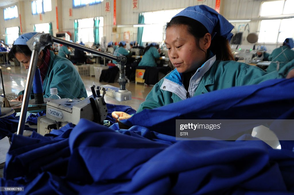 To go with 'China-economy-growth,ANALYSIS' by Kelly Olsen This picture taken on January 10, 2013 shows laborers working in a clothing factory in Huaibei, central China's Anhui province. China's economy is poised finally to end a long downward trend in 2013, economists polled by AFP say, as the new communist leadership vows to retool the nation's investment-led development model and promote a 'happy life' for all. CHINA