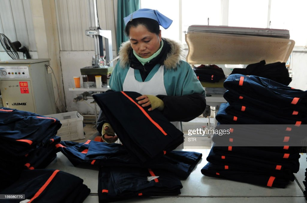 To go with 'China-economy-growth,ANALYSIS' by Kelly Olsen This picture taken on January 10, 2013 shows a woman working in a clothing factory in Huaibei, central China's Anhui province. China's economy is poised finally to end a long downward trend in 2013, economists polled by AFP say, as the new communist leadership vows to retool the nation's investment-led development model and promote a 'happy life' for all. CHINA