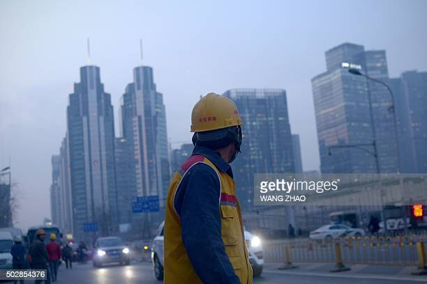 To go with CHINAECONOMYPOLITICSPROPERTYMIGRATIONURBAN by Fran WANG This picture taken on December 28 2015 shows a Chinese worker looking on as he...