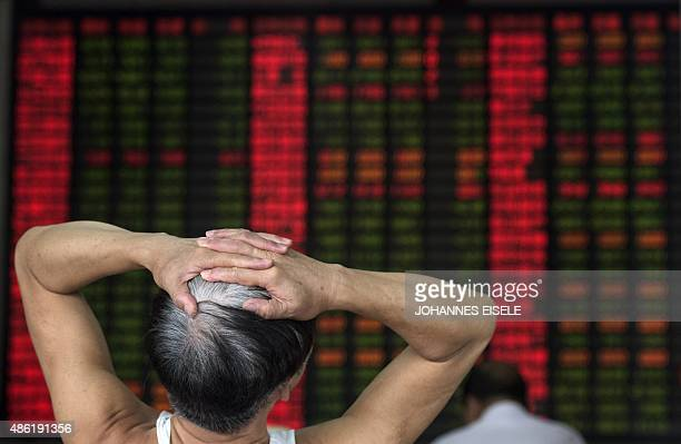 To go with ChinaeconomystockspolicyFOCUS by Bill SAVADOVE In this photo taken on September 1 an investor reacts in front of a digital board showing...
