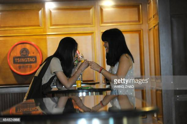 To go with ChinaGermanyJapaneconomydrinkFOCUS by Kelly OLSEN This picture taken on July 24 2014 shows two women drinking beer as they visit the...