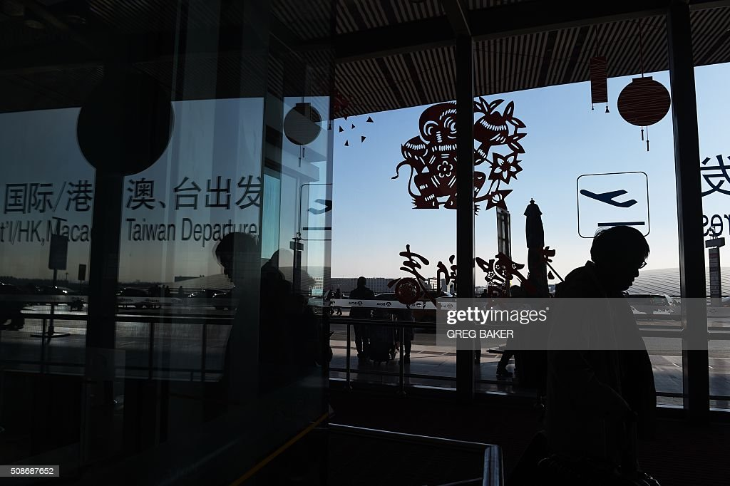 To go with China-NewYear-festival-tourism-lifestyle,FOCUS by Benjamin Carlson A traveler heads to the international departures area at the airport in Beijing on February 6, 2016 ahead of the Lunar New Year, which begins on February 8. The festival, which compares in importance to Christmas in the West, marks a time when far-flung family members return home for merriment and meals -- according to tradition, they must be back by midnight on the eve of the new year. But rising individualism and financial independence are seeing more and more young Chinese choose to defy custom, while at the same time tourism and outbound travel are surging. AFP PHOTO / GREG BAKER / AFP / GREG BAKER