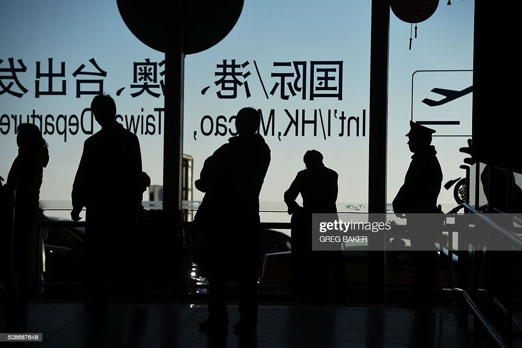To go with China-NewYear-festival-tourism-lifestyle,FOCUS by Benjamin Carlson Travelers stand near the international departures area at the airport in Beijing on February 6, 2016, ahead of the Lunar New Year, which begins on February 8. The festival, which compares in importance to Christmas in the West, marks a time when far-flung family members return home for merriment and meals -- according to tradition, they must be back by midnight on the eve of the new year. But rising individualism and financial independence are seeing more and more young Chinese choose to defy custom, while at the same time tourism and outbound travel are surging. AFP PHOTO / GREG BAKER / AFP / GREG BAKER
