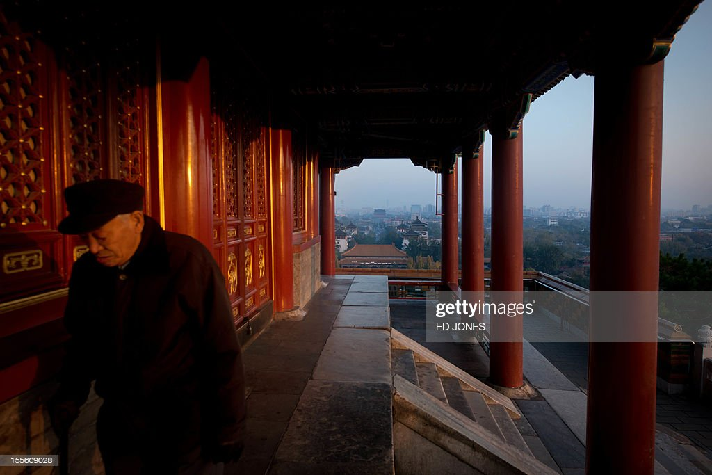 To go with China-politics-congress, ADVANCER by Patrick Lescot A man walks beside a temple in Jingshan park above the Beijing skyline early on November 6, 2012. The heirs of Mao Zedong convene this week to anoint China's next leaders, as the Communist Party maintains an iron grip on the economic powerhouse despite mounting calls for change in the Internet era. AFP PHOTO / Ed Jones