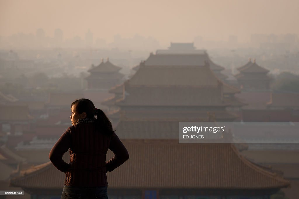 To go with China-politics-congress, ADVANCER by Patrick Lescot A woman looks out across the Forbidden City and the Beijing skyline early on November 6, 2012. The heirs of Mao Zedong convene this week to anoint China's next leaders, as the Communist Party maintains an iron grip on the economic powerhouse despite mounting calls for change in the Internet era. AFP PHOTO / Ed Jones