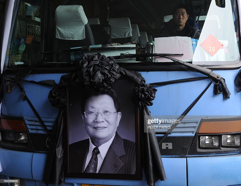 To go with 'CHINA-SOCIAL-ECONOMY-POLITICS' story by Bill Savadove A photo of dead retired Communist Party chief, Wu Renbao is seen on a bus carring mourners to his funeral in the village of Huaxi on March 22, 2013. Residents of China's 'richest village' bid farewell to the man who made Huaxi a socialist paradise, with a 20-vehicle funeral procession transporting his coffin after he died on 18 March of cancer aged 84. AFP PHOTO/Peter PARKS