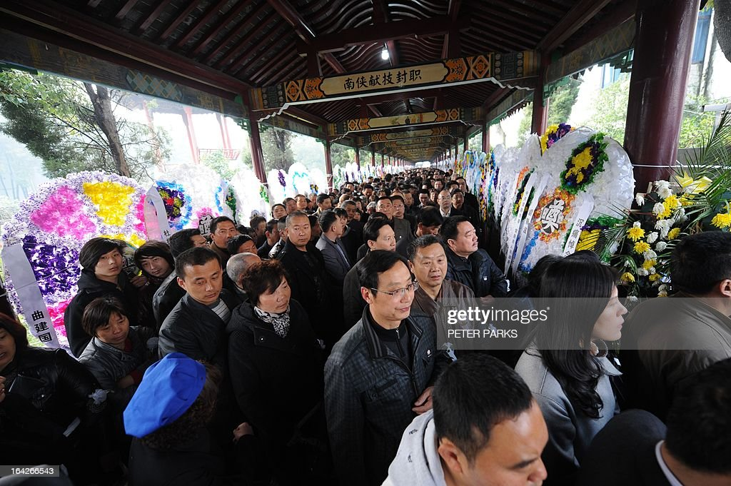 To go with 'CHINA-SOCIAL-ECONOMY-POLITICS' story by Bill Savadove Mourners queue to pay their respects to dead retired Communist Party chief, Wu Renbao before his funeral in the village of Huaxi on March 22, 2013. Residents of China's 'richest village' bid farewell to the man who made Huaxi a socialist paradise, with a 20-vehicle funeral procession transporting his coffin after he died on 18 March of cancer aged 84. AFP PHOTO/Peter PARKS