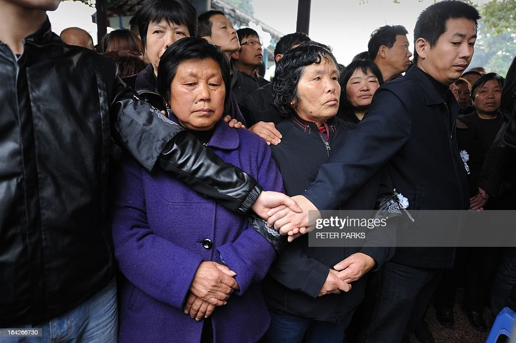 To go with 'CHINA-SOCIAL-ECONOMY-POLITICS' story by Bill Savadove Mourners are held back as they wait to pay their respects to dead retired Communist Party chief, Wu Renbao before his funeral in the village of Huaxi on March 22, 2013. Residents of China's 'richest village' bid farewell to the man who made Huaxi a socialist paradise, with a 20-vehicle funeral procession transporting his coffin after he died on 18 March of cancer aged 84. AFP PHOTO/Peter PARKS